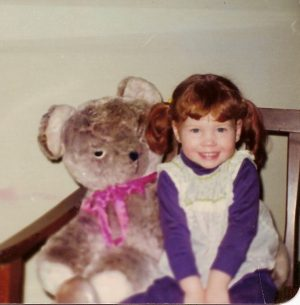 Little girl sitting with large teddy bear