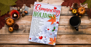 book (book cover of Romancing the Holidays Volume Two) sitting on table with fall decorations